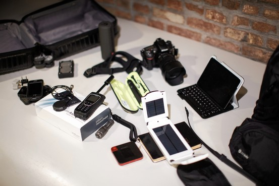 Clockwise from left, smartphones, satellite phone with external antenna, electric toothbrush, camera, iPad Mini, solar charger and mobile hot spot. Ramsay de Give for The Wall Street Journal